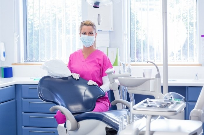 Dentist in mask looking at camera beside chair at the dental clinic-936583-edited.jpeg