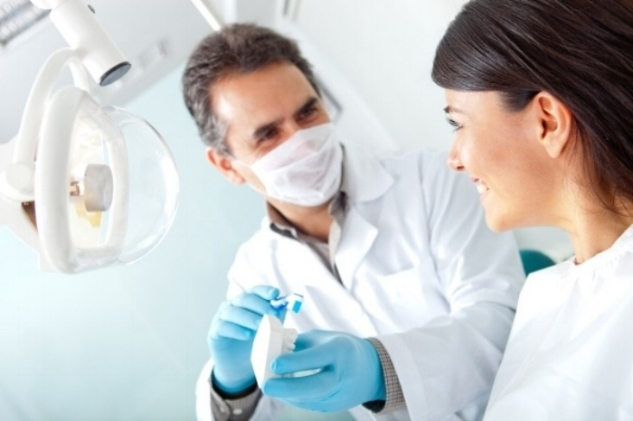 Dentist showing a woman how to brush her teeth on prosthesis-261492-edited-976710-edited.jpeg