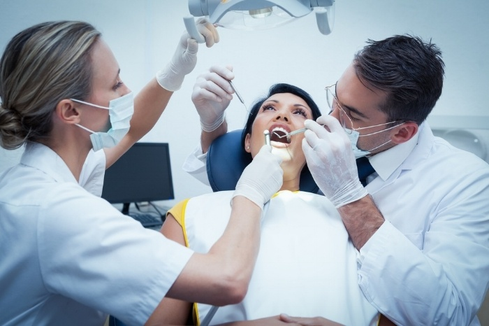 Male dentist with assistant examining womans teeth in the dentists chair-887089-edited.jpeg