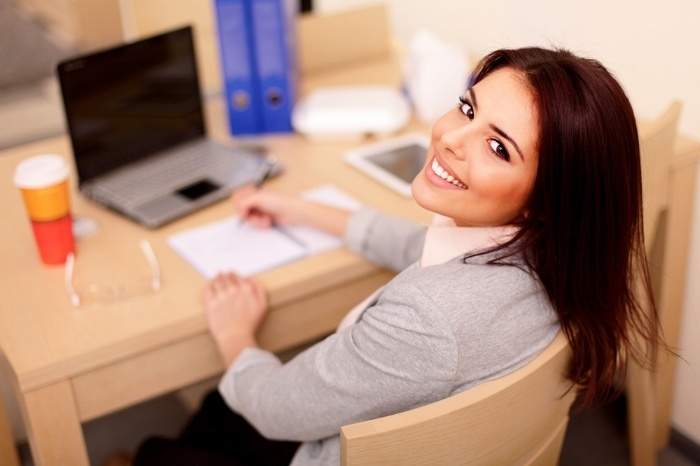 Young businesswoman sitting at desk and working. Smiling and looking back at camera-606907-edited.jpeg