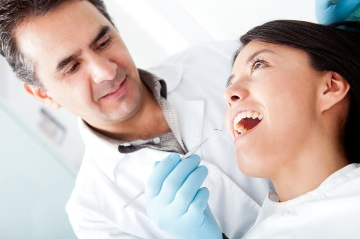 Dentist working on a female patient at his practice-499708-edited.jpeg